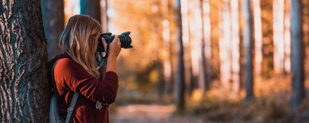 girl taking photo in forest